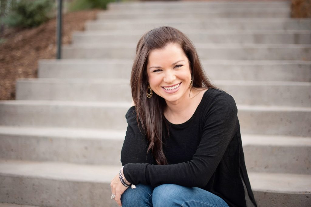 Kaycie LaGrone the interior designer, sitting on concrete steps smiling with her long, brown hair falling down past her shoulders.
